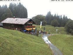 Die Berghütte mit den Bergen dahinter