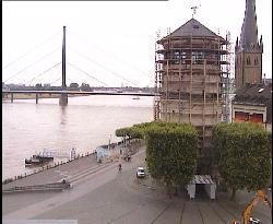Blick auf den Burgplatz mit historischem Turm und der Oberkasseler Brücke über den Rhein.